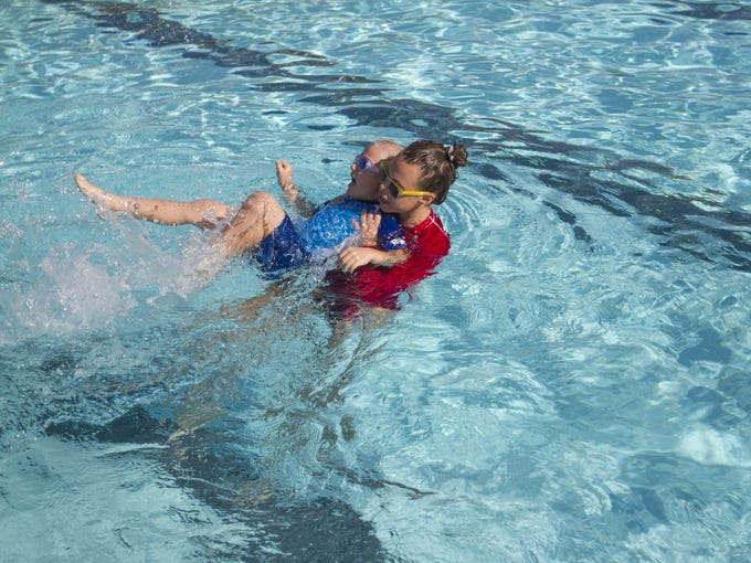 Swim Instructor Caitlyn James helps a child with swimming