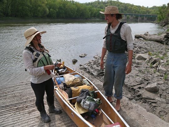 At left, the couple prepares to launch their canoe on the river Monday.