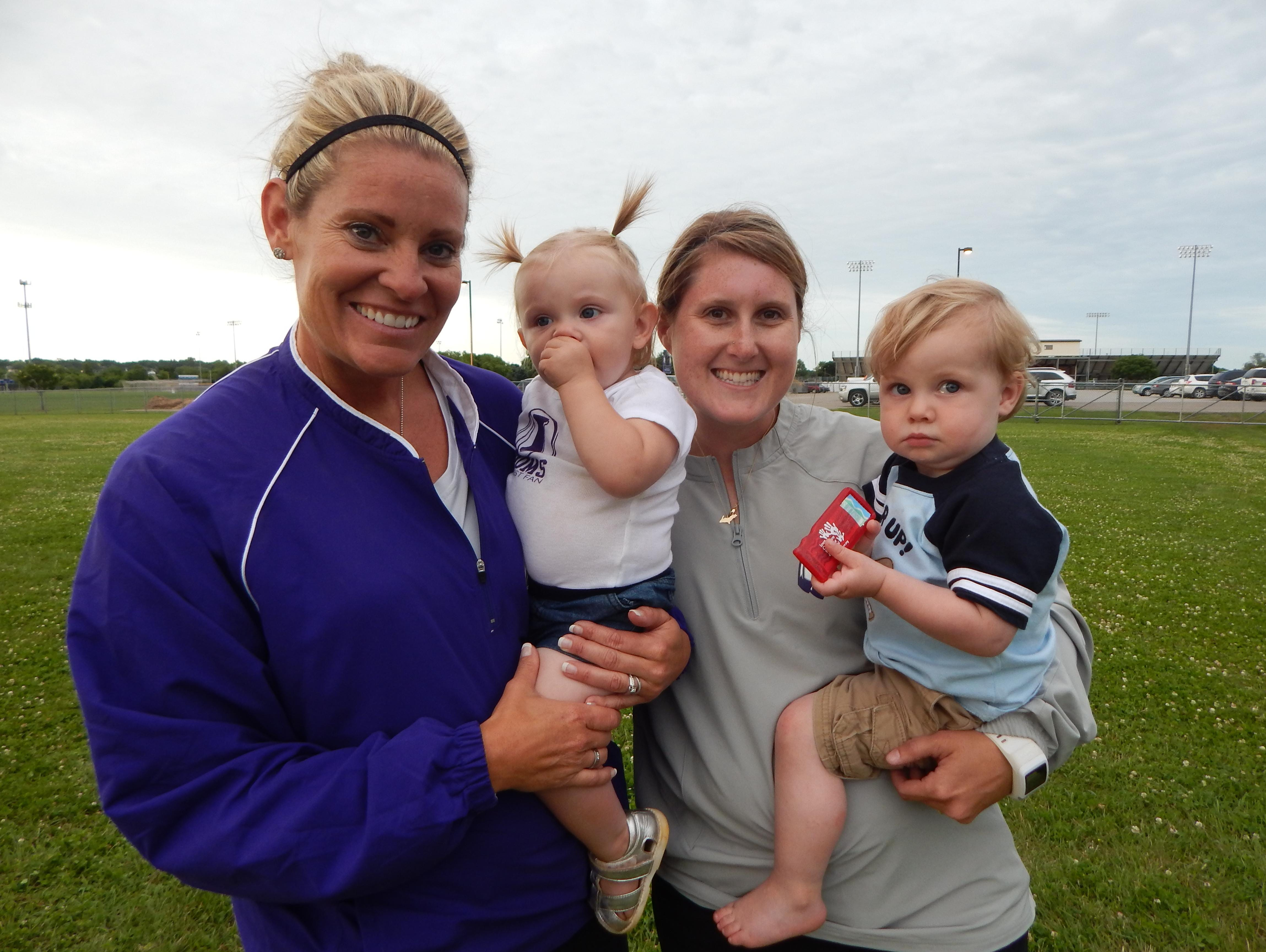 Indianola's Stacy Evans (left) and Melisse Jacobson juggle coaching softball and taking care of toddlers, too.