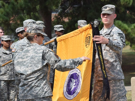 Lt. Col. Katherine Carlson (left), head of Northwestern State University's Department of Military Science, and Cadet Lt. Col. Gavin Bazer uncase the colors during an activation ceremony for the 66th Demon Battalion. The ceremony marks the beginning of the academic year in which senior Reserve Officer Training Corp (ROTC) cadets assume leadership of the battalion.