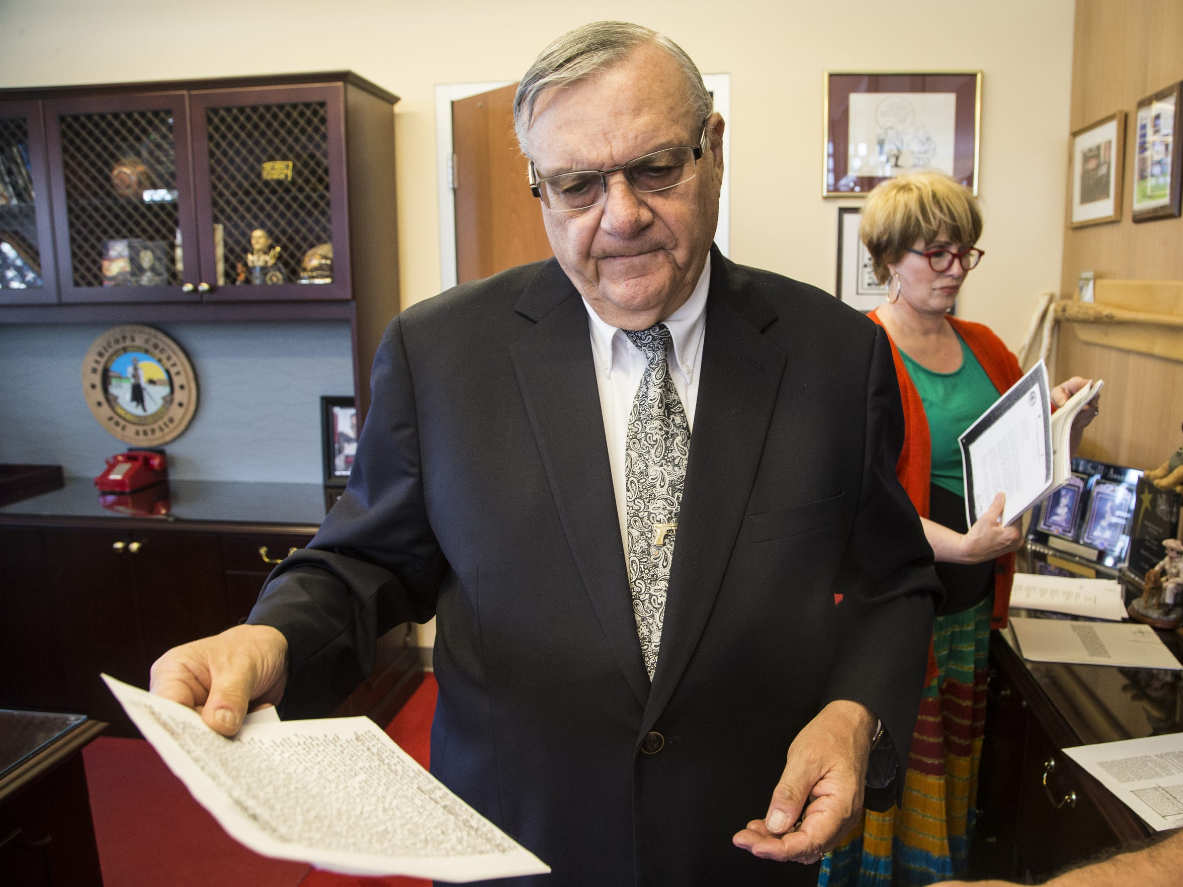 Arpaio, with Public Information Officer Lisa Allen, digs through some files that he keeps at his office from his days  in the federal Drug Enforcement Agency.
