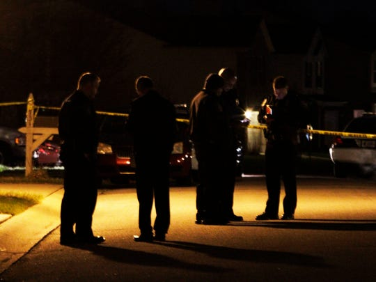 Lt. Rich Riddle (from right), Chief of Operations Brian Mahone, Police Chief Rick Hite and two  unidentifiable IMPD officers stand in the middle of the street in front of the Myers' house conferring with one another before briefing the press on the shooting.