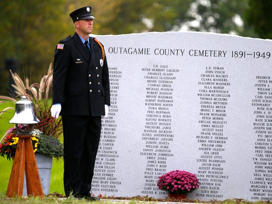 Robert Buettner of the Grand Chute Fire Department sounds the bell while the 133 names of those buried at the Outagamie County Cemetery are read during its memorial dedication Thursday, Sept. 24, in Grand Chute.