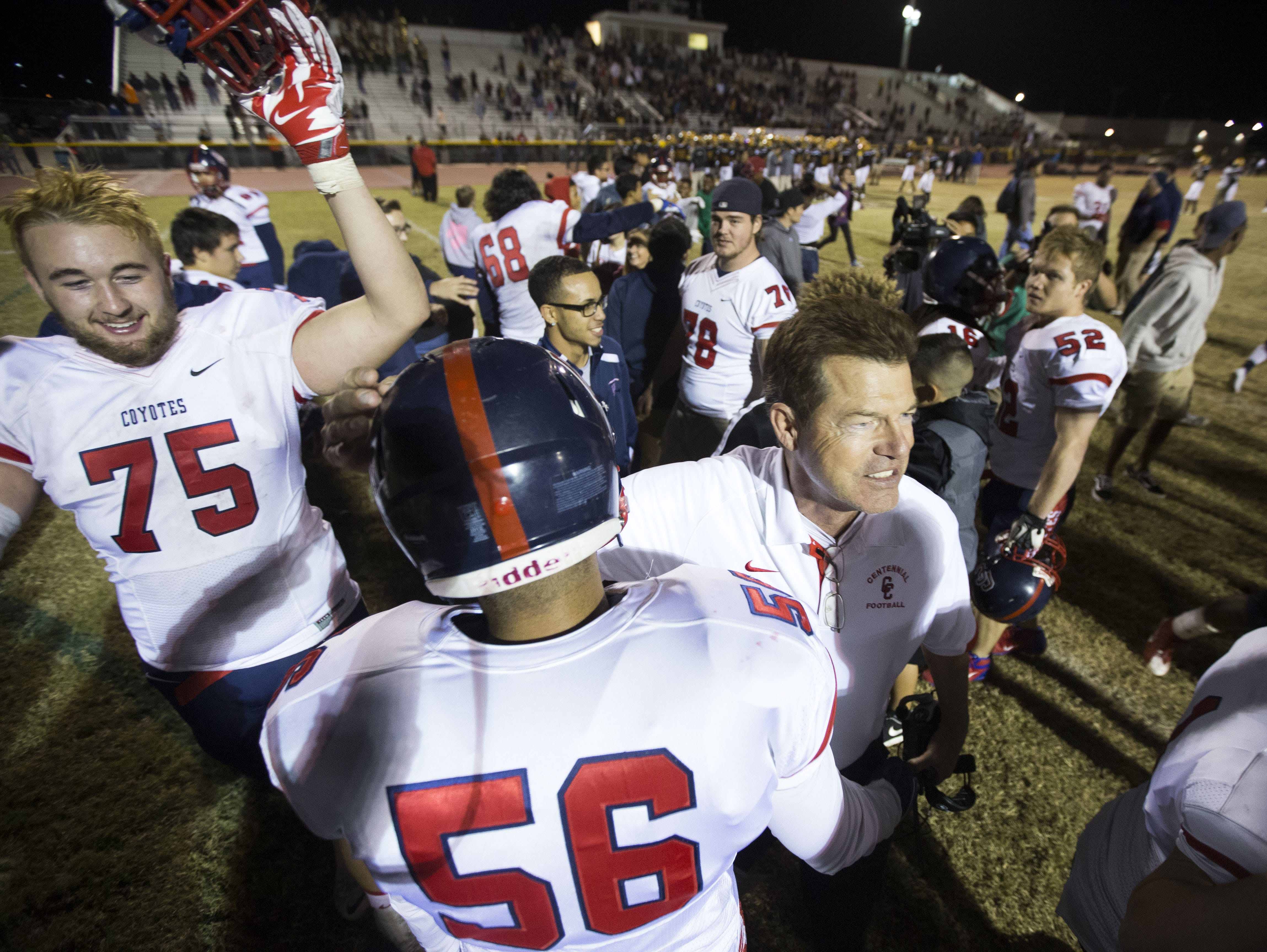Centennial's head coach Richard Taylor celebrates with Franky Ortiz (56) and Tanner Hawthorne (75) after a 31-21 win over Mountain Pointe during the Division I state semifinals at Desert Vista High School in Phoenix, AZ on November 20, 2015.