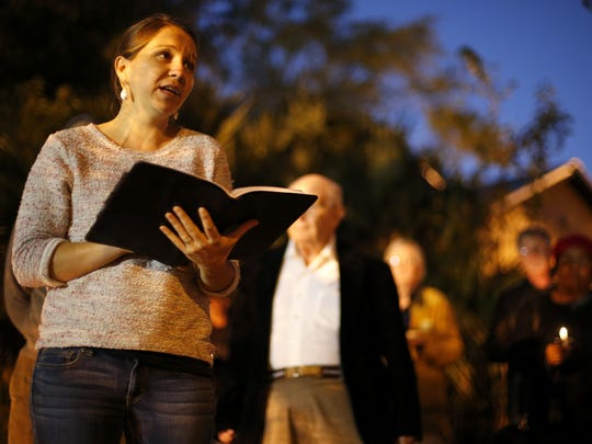 Johanne Deremble, the academic director of Alliance Française de Tallahassee, reads the names of victims of the recent terrorist attacks in Paris during a vigil held at Lake Ella on Sunday.