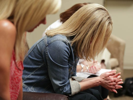 Stripped Free founders Stefanie Jeffers (left) and Kim Tabor lead a prayer for the prayer team at  Mount Pleasant Christian Church in Greenwood to close out a meeting, June 4, 2015.
