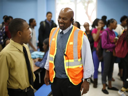 Coach Ewell Carter, Rickards' behavioral specialist, chats with Senior Jarvis Kinder during lunch at the school on 'Gentlemen's Day', Wednesday, Nov. 18, 2015, where students are encouraged to dress in collared shirts and ties and perform gentlemanly duties such as carrying books, opening doors, and using ma'am and sir to address their elders.