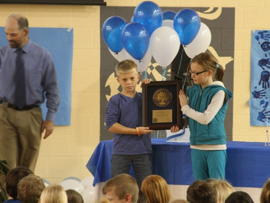 Davis Principal Jeff Kirby, far left, presented the Blue Ribbon Award plaque to Davis Elementary students, from left, Jack Hoops, a third grade student in Ellie Arseneault's class, and Taylor Alsip, a fourth grade student in Kristin Wheeler's class, at an assembly on Tuesday, Dec. 15.