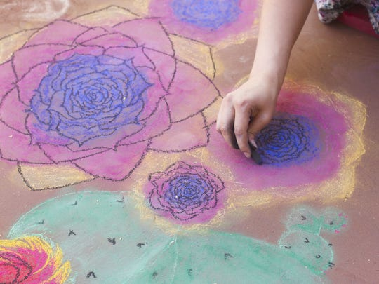 Katy Mae Goodson of Tucson paints flowers on her square