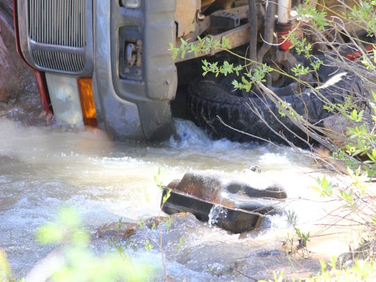 A red Ford full-size pickup rests in Coal Creek after