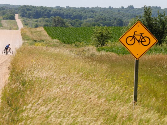 A cyclist crosses a gravel road near Panora during the third annual Bacoon Ride on the Raccoon River Valley bicycle trail on Saturday, June 18, 2016.