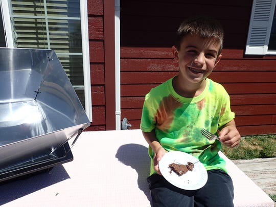 Sam Grisak enjoys a brownie fresh from the solar box oven.
