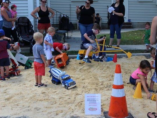 Children play in the sandpit that was made for the Touch A Truck event.