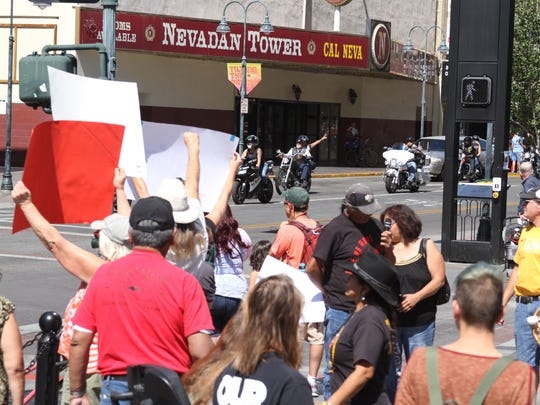 Bikers commemorating 9/11  hold up peace signs as they pass protesters at the Reno City Plaza.