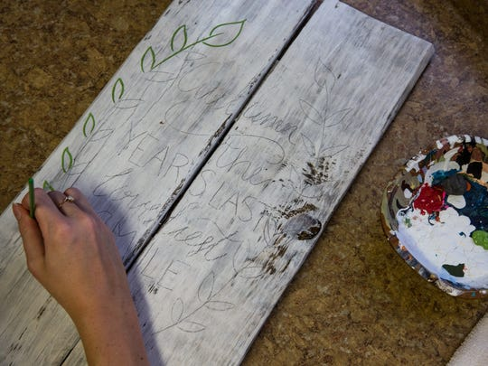 Kaitlyn Hutchinson paints a handmade wood panel sign in her home work space on Sunday, Sept. 11, 2016 in Naples, Florida. Hutchinson owns Kanndid Kreations, a business she started last year to sellÊher handcrafted, rustic artwork online and at craft fairs across the state.