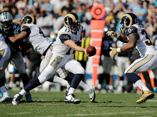 Los Angeles Rams quarterback Case Keenum, left, hands off to Los Angeles Rams running back Todd Gurley during an NFL football game against the Carolina Panthers, Sunday, Nov. 6, 2016, in Los Angeles.