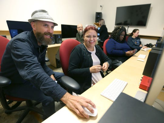 Jamie Harmon works with student Luz Delia Gomez during a photography imaging class in the Crosstown Arts digital art making lab, which is free and open to anyone.