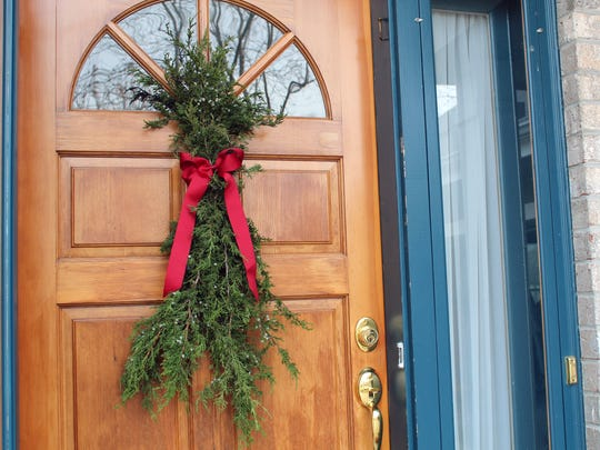 It's easy and nearly free to make your own  Christmas door swag using greenery pruned from your yard.