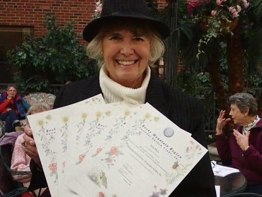 Patty Schlaeger holds up the awards Rainbow Garden