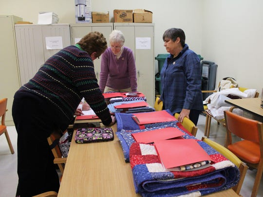 Members of the Quilts of Valor Foundation prepare the quilts to be presented.