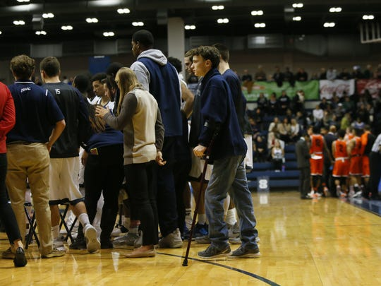 Matt Tomaino stands with the rest of the Monmouth University basketball team during a timeout against Princeton in 2016.