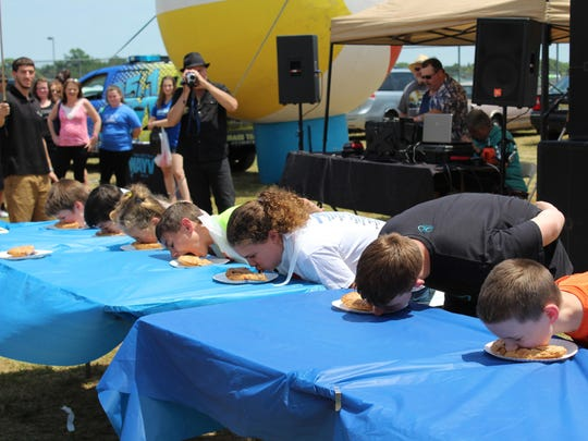The pie eating contest is a tradition of the Red, White and Blueberry Festival, where each contestant goes through several blueberry pies before a winner is declared.