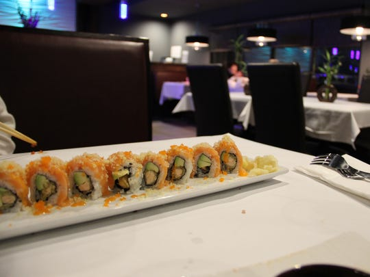 The Salmon Lover roll at Nagoya Japanese Steakhouse & Sushi is filled with tempura salmon and avocado, topped with pieces of fresh raw salmon.