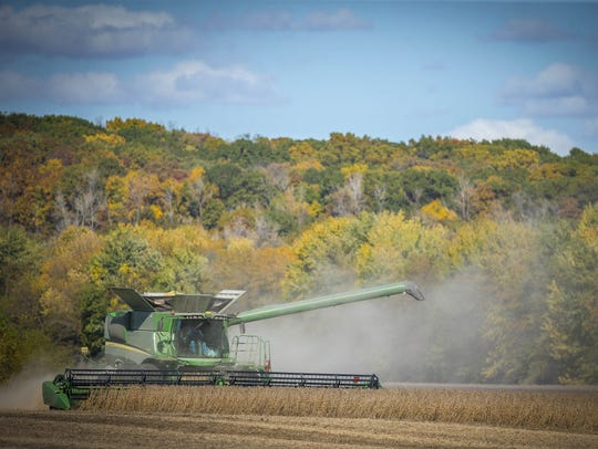 Howard Goodhue combines soybeans near Carlisle in 2016. China is the largest buyer of U.S. soybeans and second-largest buyer of pork, based on weight. Iowa is the nation's largest pork producer and second-largest soybean producer.