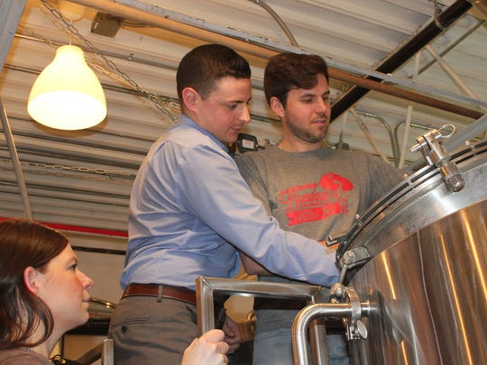 Johanna Lester, left, looks on as Alex Amorese, center, and Adam Carey from Gilda's Club Rochester help brew at Roc Brewing Company.
