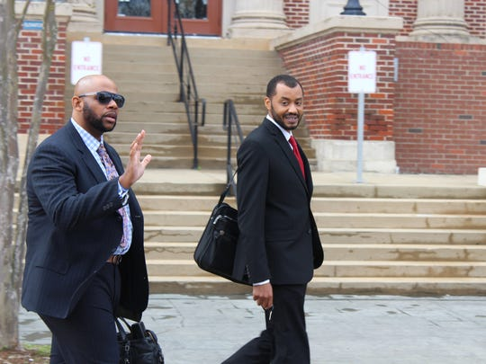 Jonathan Goins (left) waves as he and co-counsel Christopher LaCour (right) leave the Avoyelles Parish Courthouse on Monday. Goins said they were happy with the first day of jury selection in the trial of their client, Derrick Stafford.