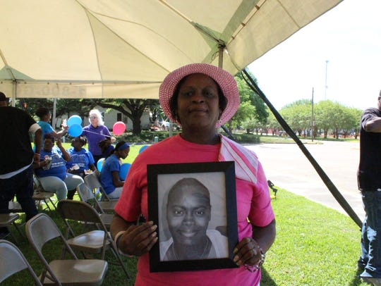 Edna Robinson holds a photo of her daughter, 31-year-old
