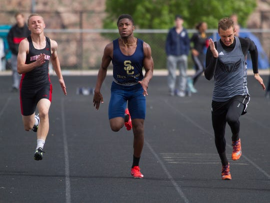 Snow Canyon's Tae Washington (left) races in a Region 9 track meet in 2017.