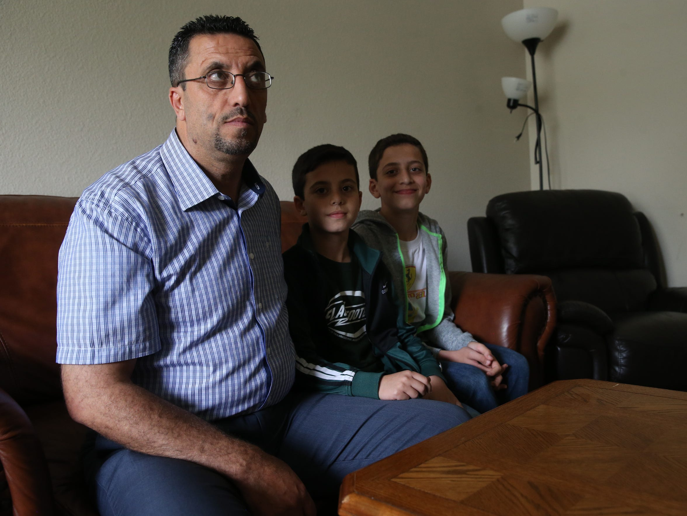 Safouh Alhendi sits with his two sons Mohammad Noor,