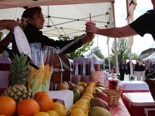Lucy Wills, of Molalla, hands a thirsty patron fresh-squeezed