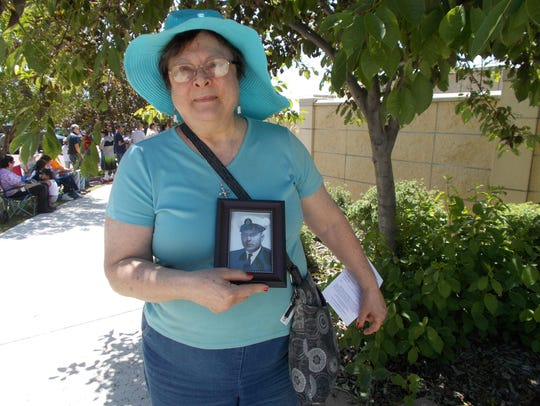 Marcia Lauzon stands with a photo of her late husband,