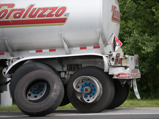 The rear left wheel and back end of a tanker truck