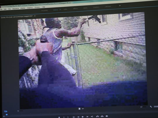 This frame from Dominique Heaggan-Brown's body camera video shows Sylville Smith being shot in the right biceps as Smith throws his gun over a fence. Less than two seconds later Heaggan-Brown fires a second shot while Smith is on the ground, killing him.