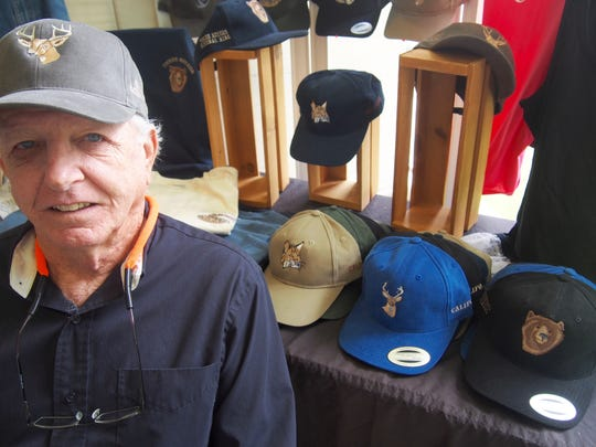 Ted Fox embroiders designs on baseball caps.