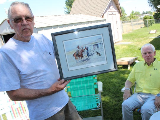 Jim Thoroughman holds a print of a Charlie Russell's