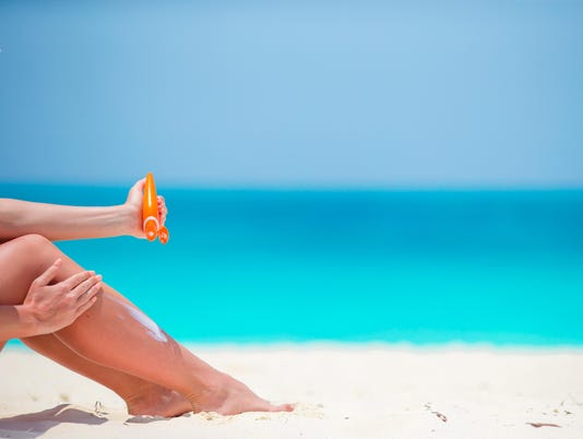 Legs of young girl applying sunblock while sitting on beach
