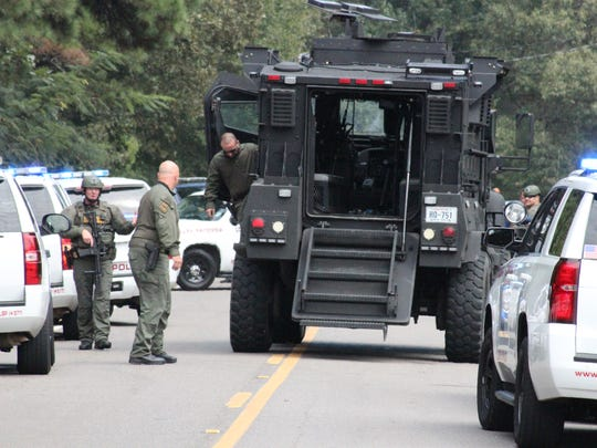 SWAT members gather near a Louisiana State Police vehicle Wednesday morning at the scene of a standoff in the Ruby area. The standoff ended peacefully.