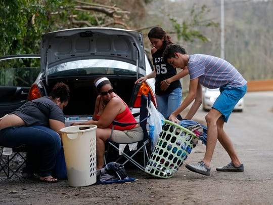 A family washes clothes on the side of the road, utilizing