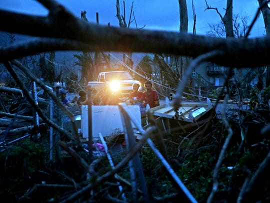 Evan Mandino, right, sits with neighbors on a couch outside their destroyed homes as sun sets in the aftermath of Hurricane Maria, in Yabucoa, Puerto Rico, on Sept. 26, 2017.