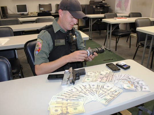 Sheriff's Deputy Matt Kunce checks the contents of a pipe for evidence. The counterfeit money and methamphetamine were seized during a traffic stop from a felon.