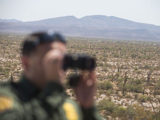 A federal agent looks for traces of a migrant who was illegally crossing the U.S. border near Ajo, Arizona.