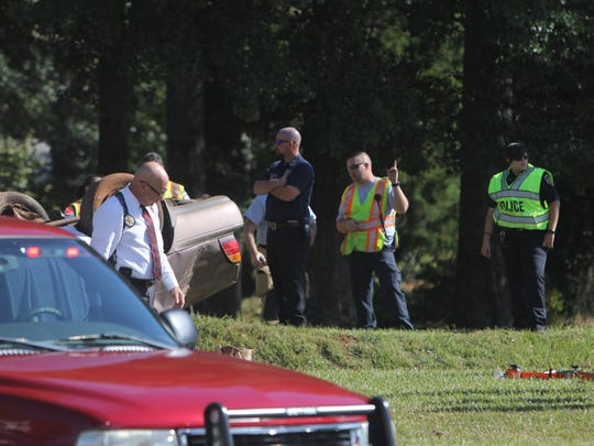 Anderson County Deputy Coroner Don McCown, left, walks near a fatal wreck Monday morning on Shockley Ferry Road across from a cemetery.