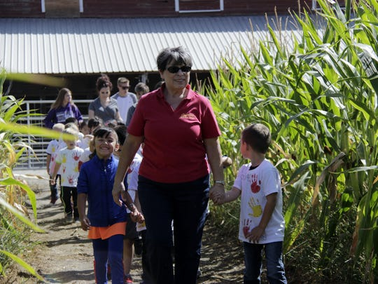 Cypress Elementary School kindergarten teacher Cathy Stoddard leads her class through the corn maze at the Tulare high school farm Tuesday morning.