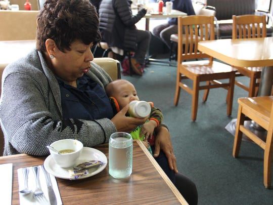 Marilyn Williams feeds great-grandson Benjamin Xavier