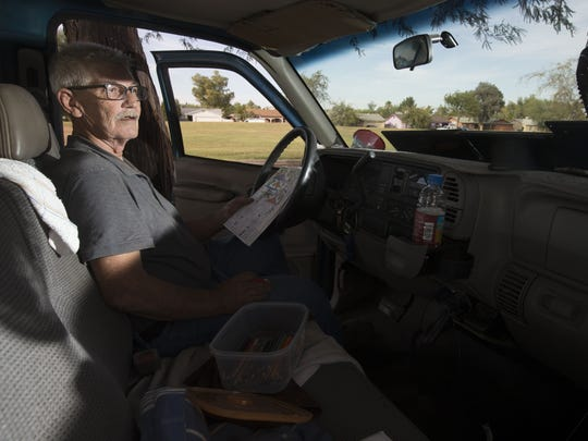 Daniel Runyan, who lives in his truck, is parked at a west Phoenix park. He uses a fan to cool himself off from the heat.