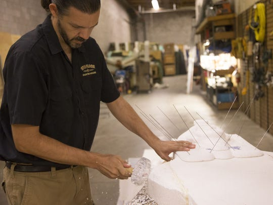 Jacob Redwood, general manager of the13th Floor, Haunted House in Phoenix, works on an Egyptian sarcophagus cut out of foam.